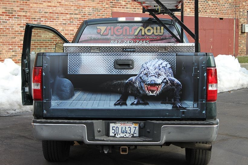 Truck tailgate with image applied to look like tailgate is off and there is a menacing alligator looking back at you.