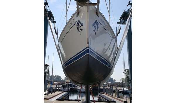 Head on shot of boat in travel lift hoist with horse graphics at bow of sailboat. Waukegan, IL