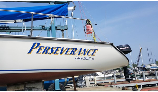 Lettering on port side of sailboat in Vivid Blue with Yellow drop shadow