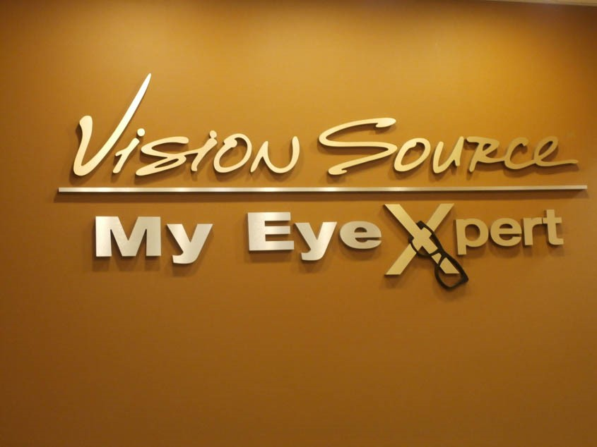 Custom dimensional raised foam logo lettering with gold faces and a pair of eye glasses on wall behind reception desk at an eye doctor's office in Gurnee