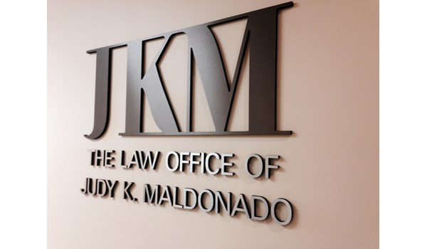 Bronze and Gun Metal Gray dimensional lettering and logo on wall of law practice in Gurnee IL