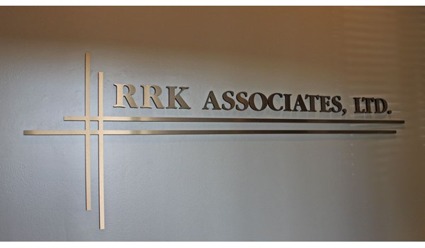 Metallic faced dimensional wall lettering at business entrance